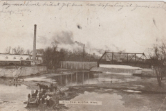 1910 picture postcard showing the Cedar River at the 4th Ave NE (old Water Street) dam. Notice the old greenhouse situated on the present-day site of Riverside Arena's parking lot