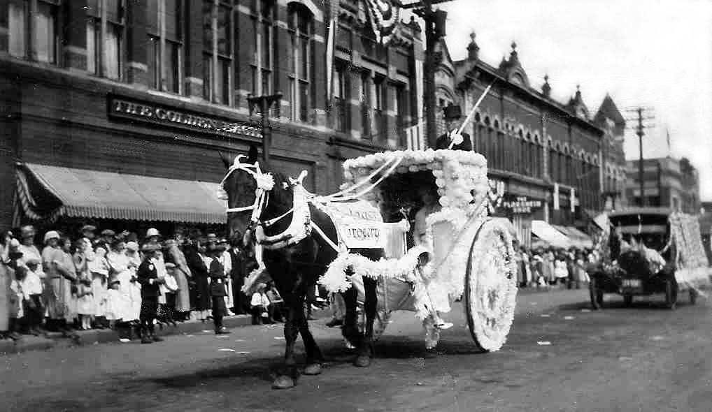 Andrew Hauge driving the Dalagar Grocery float with Mr. and Mrs. Dalagar riding down Austin's Main Street (1930)